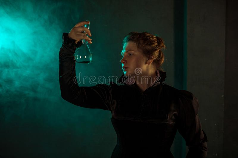 Scientist researcher with a flask of radioactive material. History of science, great physical discoveries. Image in the style of Marie Curie, concept royalty free stock photography