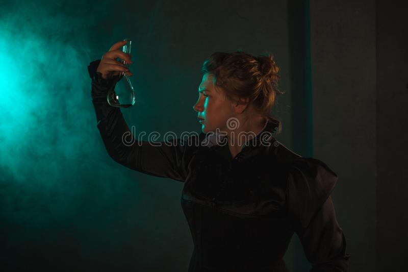 Scientist researcher with a flask of radioactive material. History of science, great physical discoveries. Image in the style of Marie Curie, concept royalty free stock image