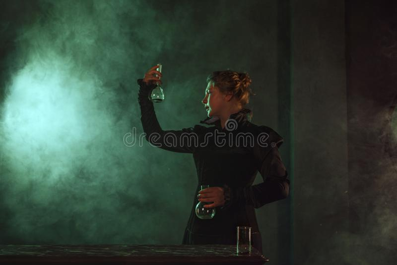 Scientist researcher with a flask of radioactive material. History of science, great physical discoveries. Image in the style of Marie Curie, concept stock image
