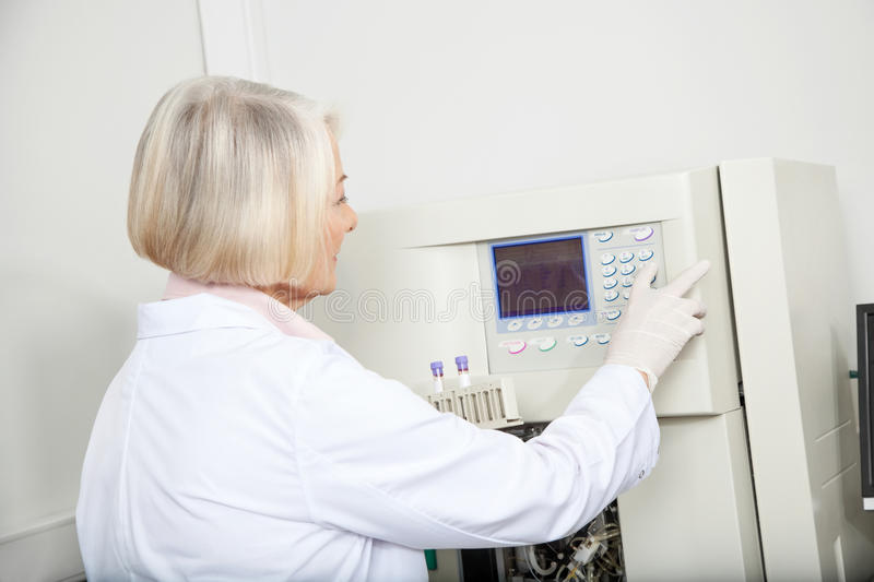 Scientist With Samples Operating Analyzer In Lab stock image