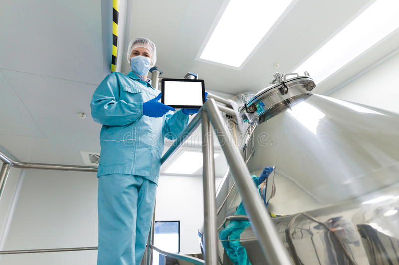Scientist show empty tablet near steel tank. Caucasian scientist in blue lab suit and gloves stand on steel ladder near chromed tank and show empty tablet stock images