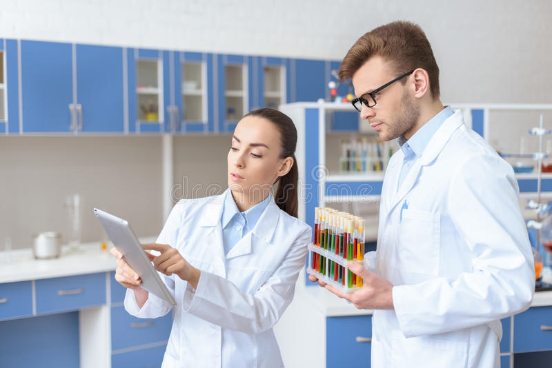 Scientist showing digital tablet to colleague holding test tubes. Young women scientist showing digital tablet to colleague holding test tubes royalty free stock images
