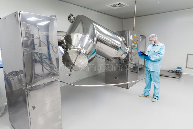 Scientist stand check readings about machine with rolling barrels. Caucasian scientist in blue lab suit and gloves check readings of big steel machine with stock image