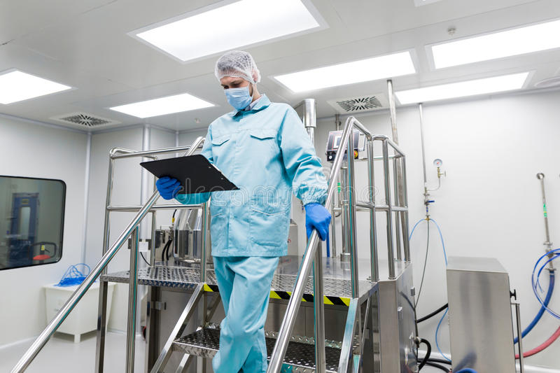 Scientist stand on metal stairs in laboratory. Caucasian scientist in blue lab suit and gloves stand on steel ladder and check readings stock image