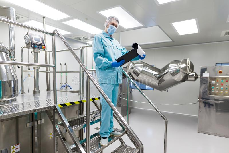 Scientist stand on metal stairs in laboratory. Caucasian scientist in blue lab suit and gloves stand on steel ladder and check readings, look at camera, turning stock photos