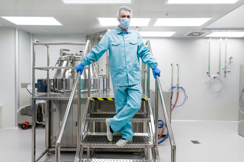 Scientist stand on metal stairs in laboratory. Caucasian scientist in blue lab suit and gloves stand on steel ladder hold hands on handrails, look at camera stock images