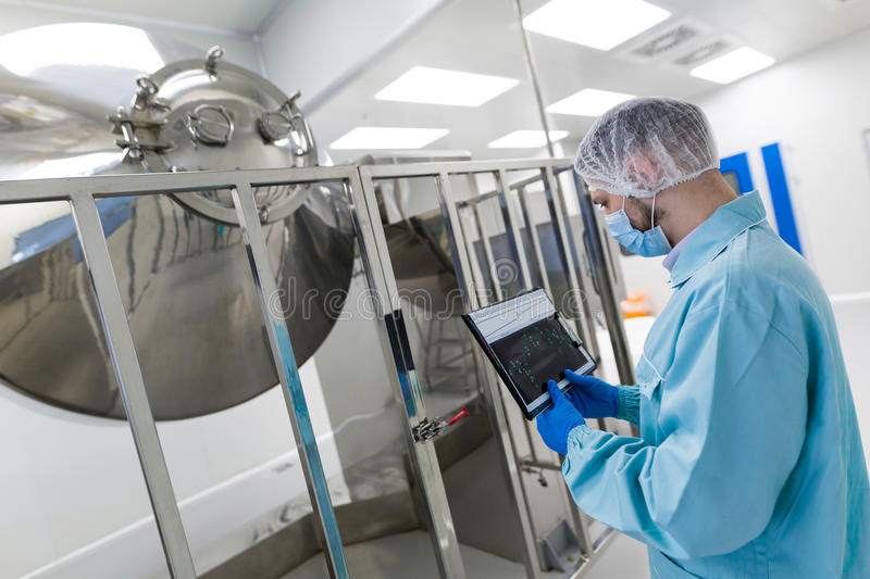 Scientist stand near chromed barrels. Caucasian scientist in blue lab uniform stand near big steel machine with big chromed tanks, look at camera, make notes stock images