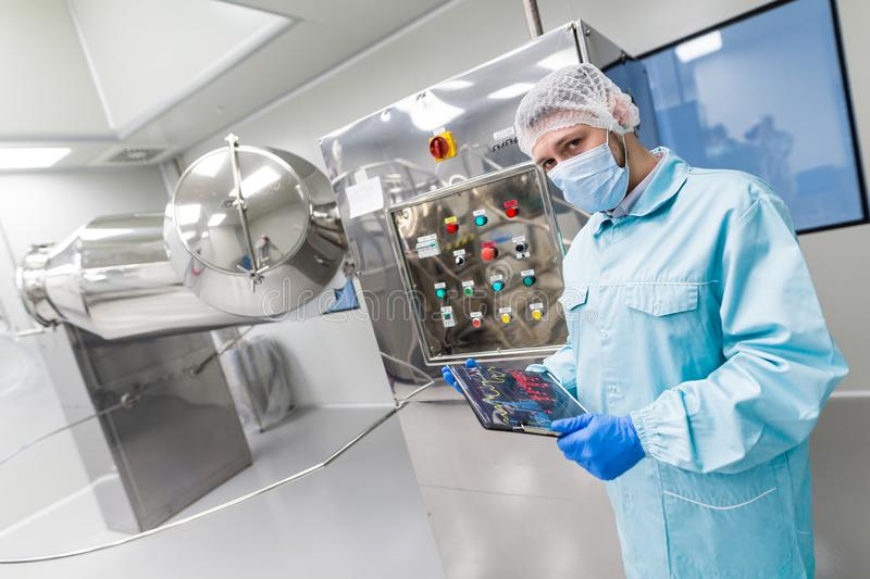 Scientist stand near control panel with buttons. Caucasian scientist in blue lab suit and gloves stand near control panel with buttons, look at camera, turning stock photography