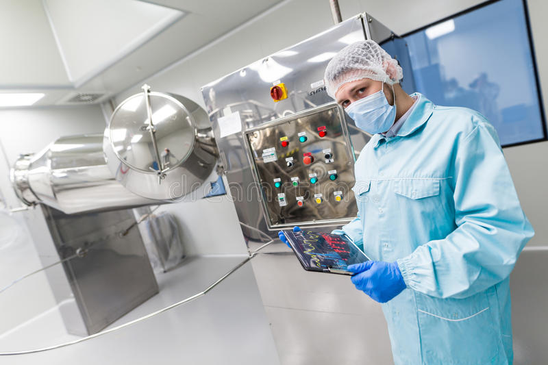 Scientist stand near control panel with buttons. Caucasian scientist in blue lab suit and gloves stand near control panel with buttons, look at camera, turning royalty free stock photography