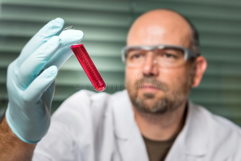 Scientist with a test tube and red liquid stock photo