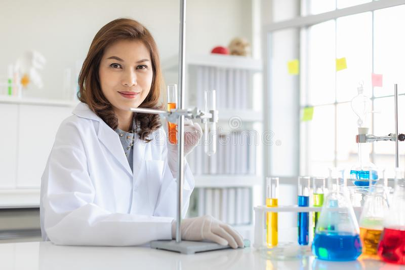 Scientist use stand to hold orange test tube royalty free stock photography