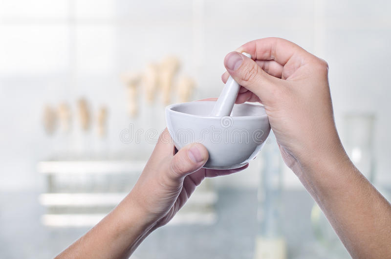 Scientist using pestle and mortar in laboratory stock photography