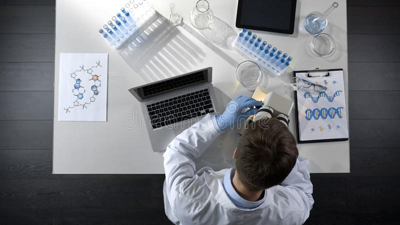 Scientist viewing samples under microscope, research for scientific article stock image