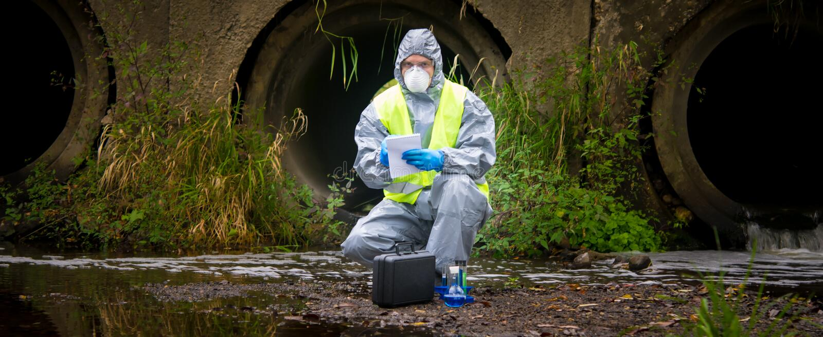 The scientist, wearing a protective suit, gloves and mask, took the liquid from the river, in test tubes, and writes the results stock photo