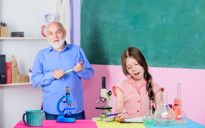 Scientist at work. mature teacher of biology. Pupil girl in school lab. Microscopy. Laboratory equipment. small girl stock images