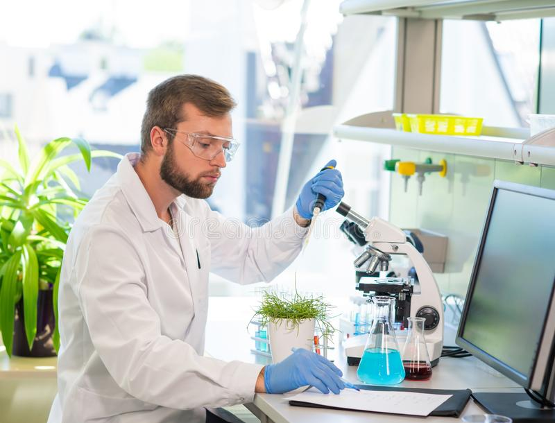 Scientist working in lab. Doctor making microbiology research. Laboratory tools: microscope, test tubes, equipment. Biotechnology, genetics, biochemistry royalty free stock photography