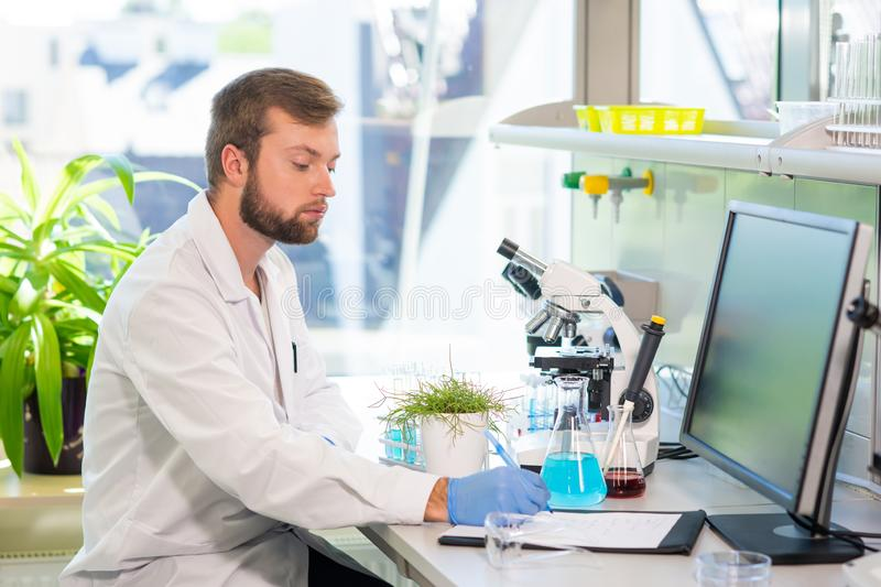 Scientist working in lab. Doctor making microbiology research. Laboratory tools: microscope, test tubes, equipment. Biotechnology, genetics, biochemistry stock photo