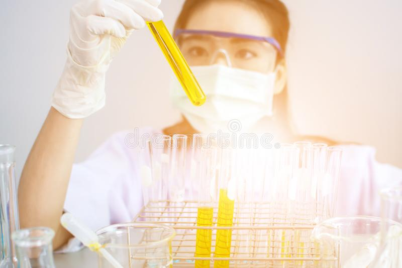 Scientist working at the laboratory. Professional distinguished Science specialist at work.Young Asian scientist with test tube making research in clinical stock photos