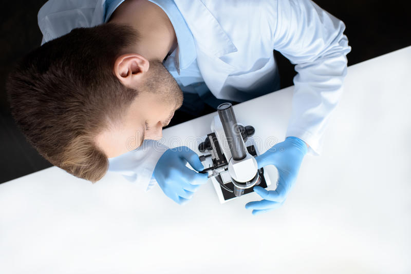 Scientist working with microscope in laboratory. Top view of scientist working with microscope in laboratory stock photography