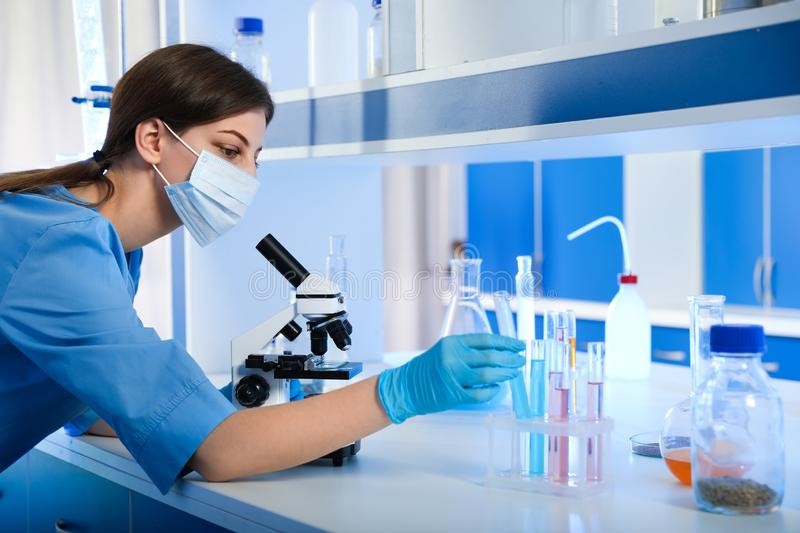 Scientist working with microscope and test tubes. Laboratory analysis royalty free stock photos