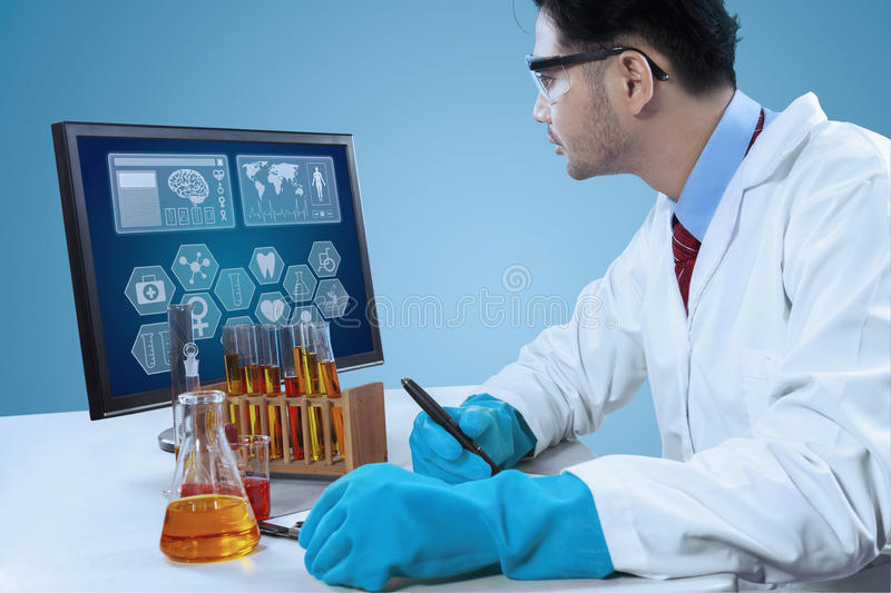 Scientist write research report. Male scientist looking at monitor and write research report on clipboard stock image