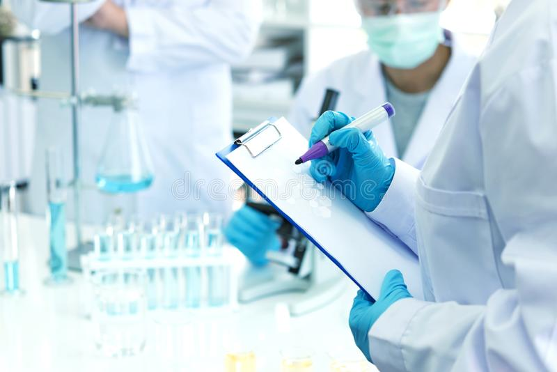Scientists analyzing study data and evaluating microscope.  Health care researchers doing some research with dropper chemical test royalty free stock photography