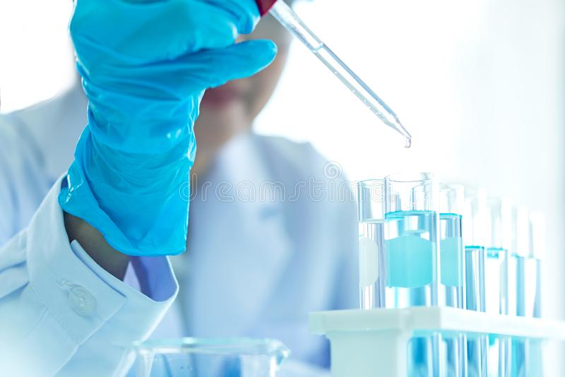 Scientists analyzing study data and evaluating microscope success for work shop. Health care researchers doing some research with dropper chemical testing in royalty free stock photo