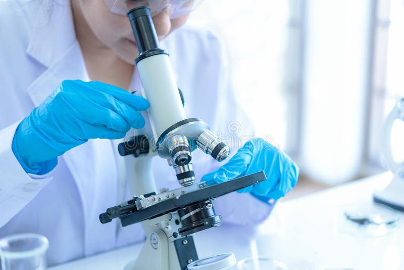 Scientists analyzing study data and evaluating. Microscope. Health care researchers doing some research with dropper chemical testing and working in life royalty free stock photos