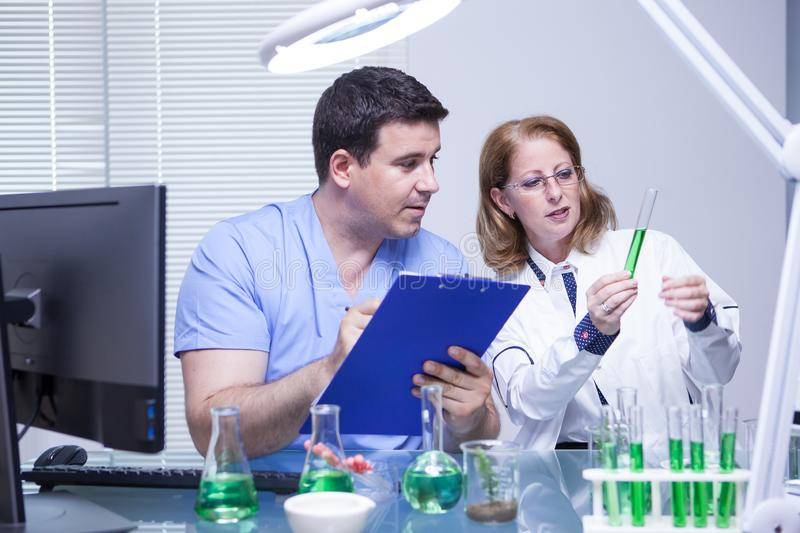 Scientists in biotechnology checking the solution from a test tube. Scientific test royalty free stock photos