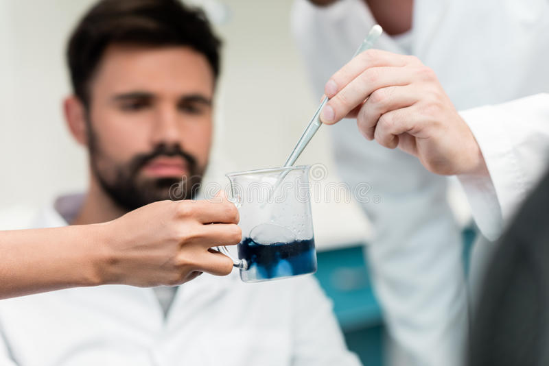 Scientists making experiment with reagent and pipette. Close-up view of scientists making experiment with reagent and pipette royalty free stock image