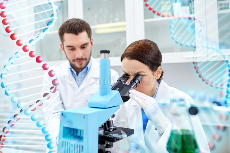 Scientists with microscope making test in lab. Science, chemistry, technology, biology and people concept - young scientists looking to sample through microscope stock image