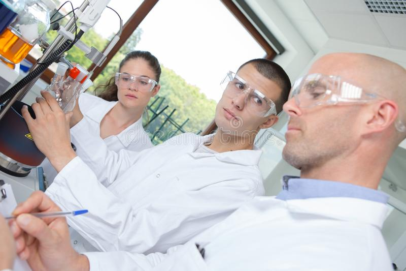 Scientists performing experiment wearing protective glasses stock photography