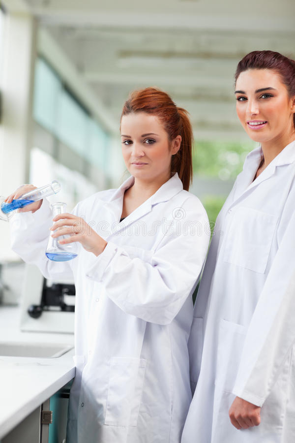 Download Scientists Pouring Blue Liquid In An Flas Stock Image - Image: 21246543