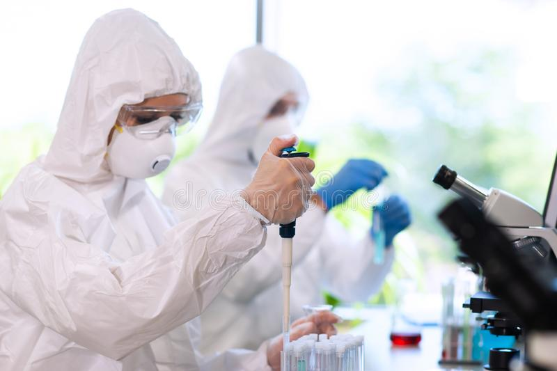 Scientists in protection suits and masks working in research lab using laboratory equipment: microscopes, test tubes. Biological hazard, pharmaceutical royalty free stock photo