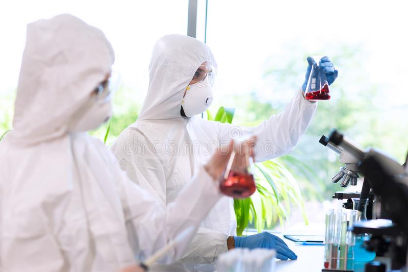 Scientists in protection suits and masks working in research lab using laboratory equipment: microscopes, test tubes. Biological hazard, pharmaceutical stock photos