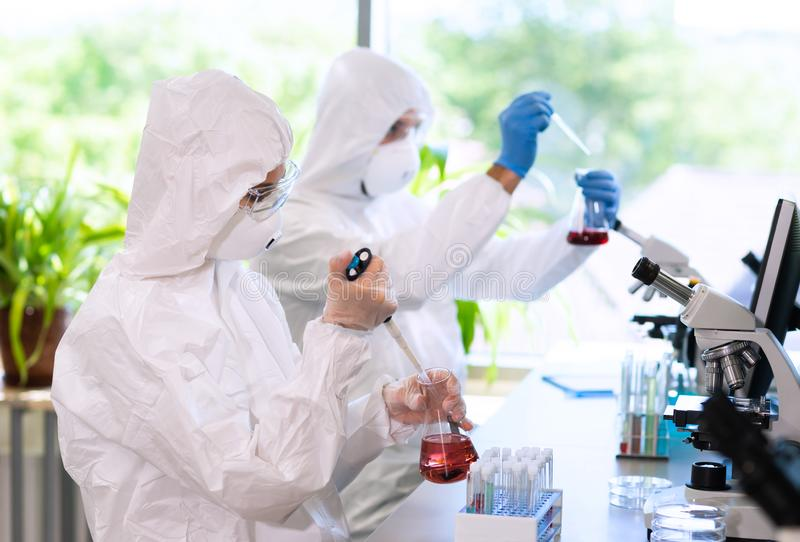 Scientists in protection suits and masks working in research lab using laboratory equipment: microscopes, test tubes. Biological hazard, pharmaceutical royalty free stock photography