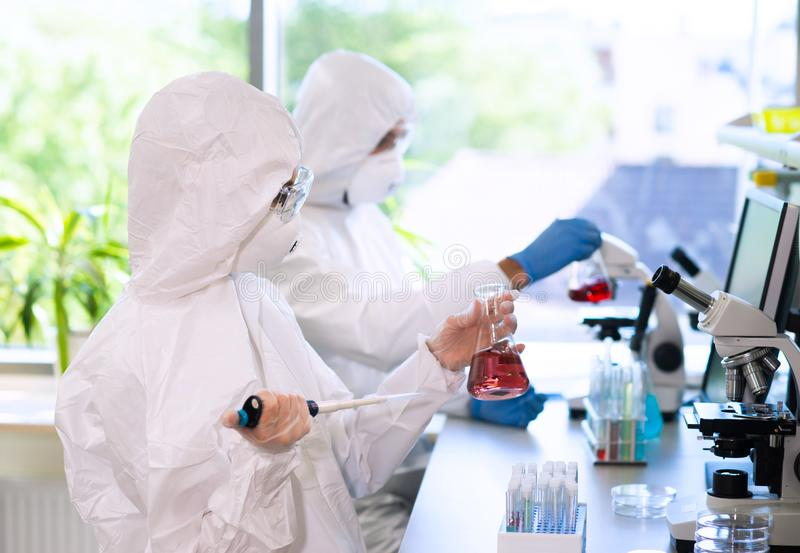 Scientists in protection suits and masks working in research lab using laboratory equipment: microscopes, test tubes. Biological hazard, pharmaceutical stock photo