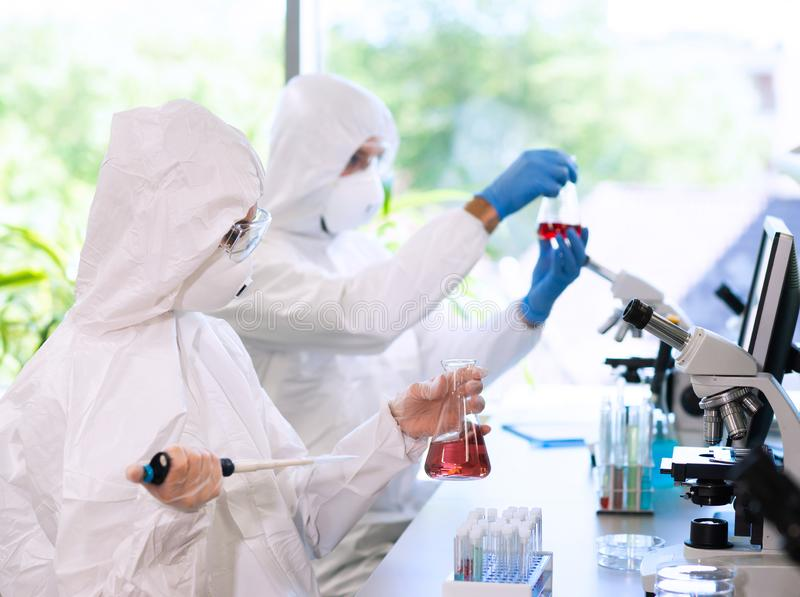 Scientists in protection suits and masks working in research lab using laboratory equipment: microscopes, test tubes. Medicine, infection and vaccine discovery royalty free stock images