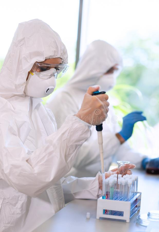 Scientists in protection suits and masks working in research lab using laboratory equipment: microscopes, test tubes. Medicine, infection and vaccine discovery royalty free stock photography