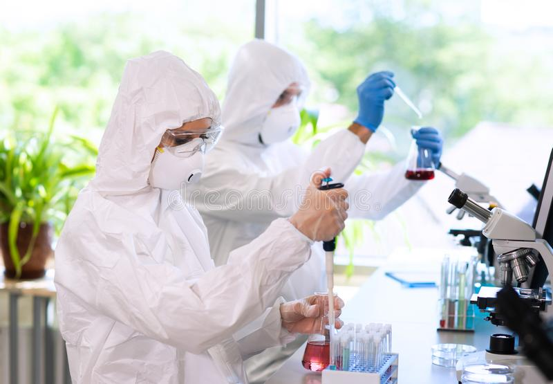 Scientists in protection suits and masks working in research lab using laboratory equipment: microscopes, test tubes. Medicine, infection and vaccine discovery royalty free stock photos