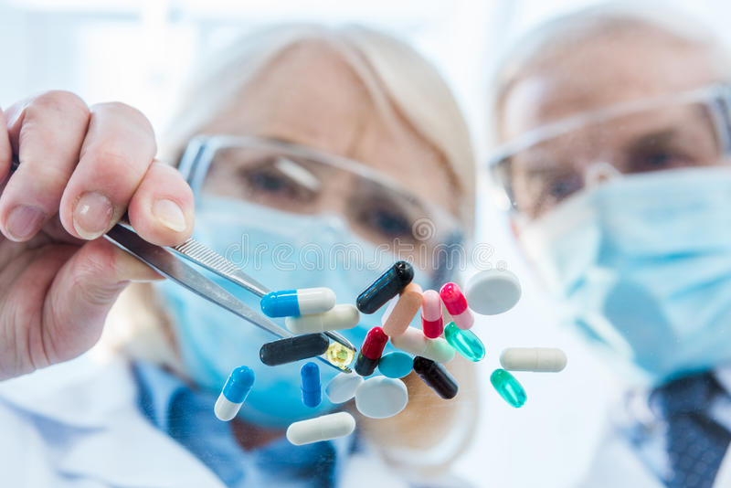Scientists in protective workwear working with various pills stock photos