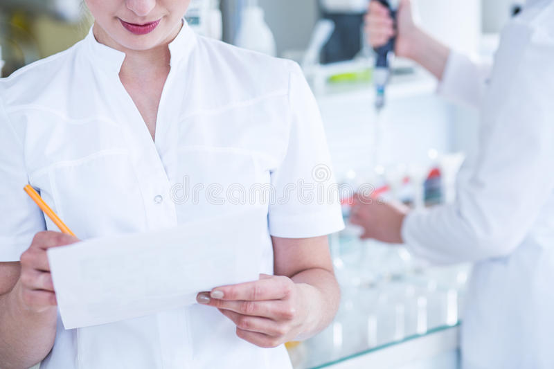 Scientists in sterile coats. Close up of two scientists in white sterile laboratory coats royalty free stock image