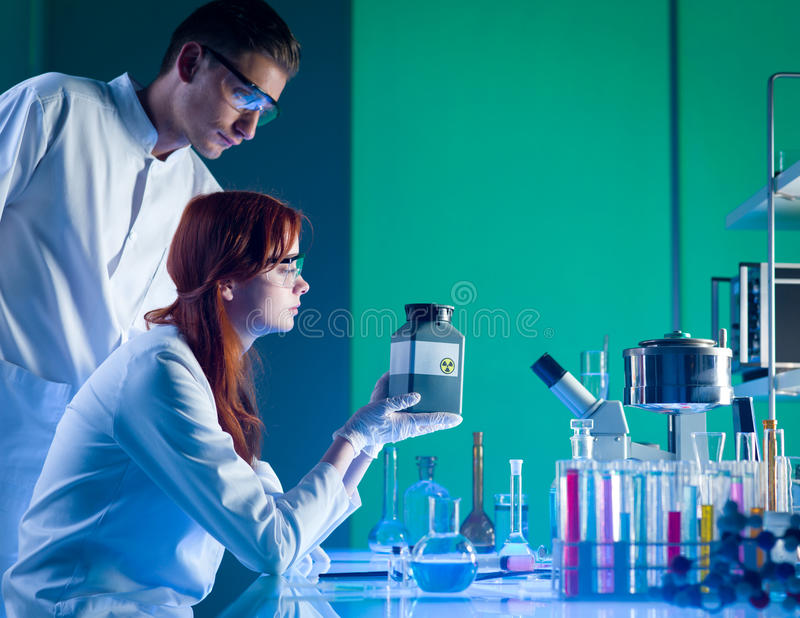 Scientists with toxic waste container. Close-up of two caucasian scientists looking at a toxic waste plastic container, in a chemistry laboratory royalty free stock images
