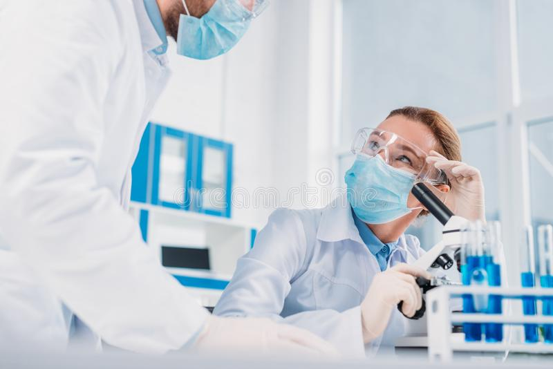 scientists in white coats, medical gloves and goggles making scientific research together stock image