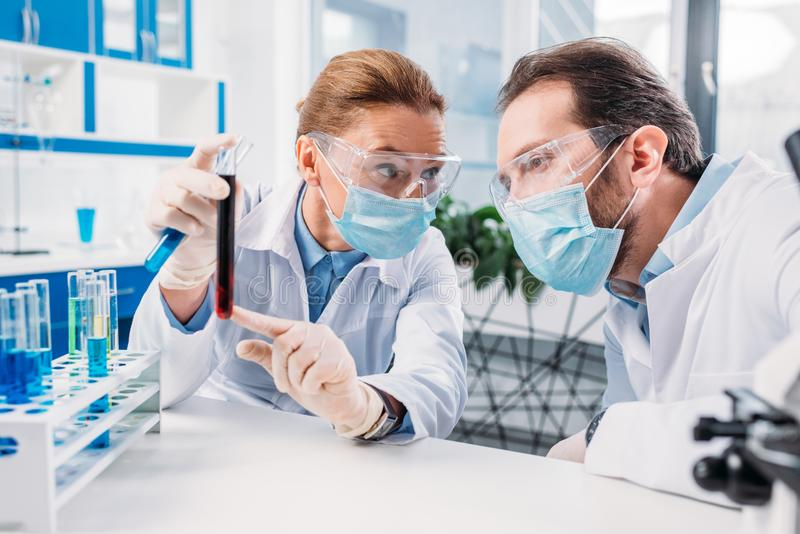 scientists in white coats and medical masks working with reagents royalty free stock photo