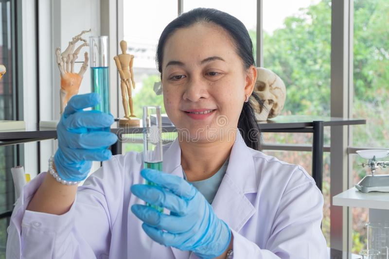 Scienziati asiatici di medio evo della donna in laboratorio r fotografie stock