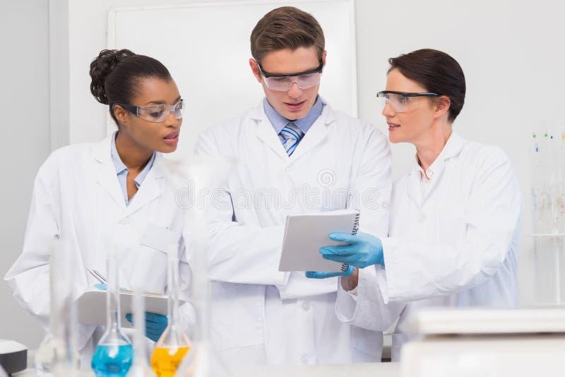 Scienziati che esaminano lavagna per appunti fotografia stock