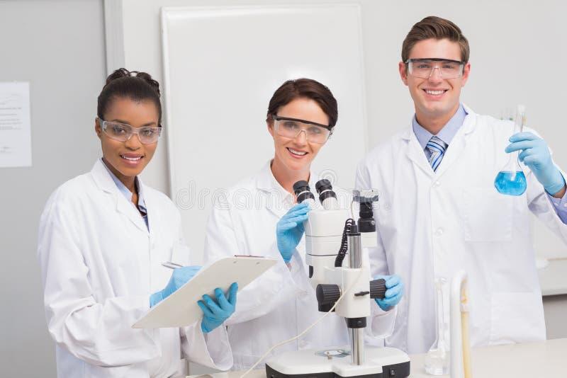 Scienziati che lavorano attentamente con il microscopio ed il becher immagine stock