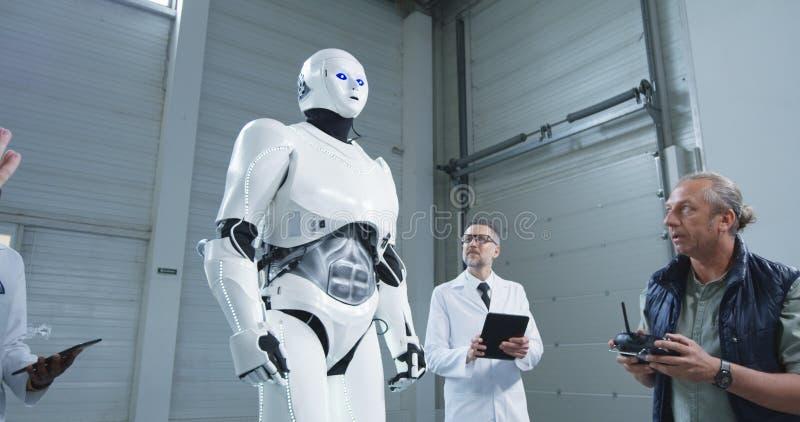 Scienziati che verificano il movimento dei robot fotografia stock libera da diritti