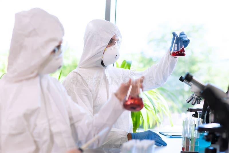 Scienziati nei vestiti di protezione e maschere che lavorano nel laboratorio di ricerca facendo uso dell'attrezzatura di laborato fotografie stock